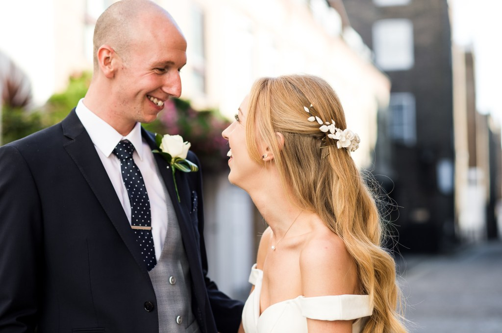 Old Marylebone Town Hall Wedding, couple smile and laughing with each other, natural wedding portrait