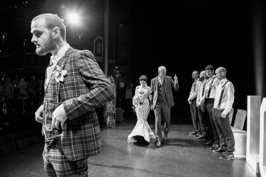 Arriving on stage to be married in a theatre © Jessica Grace Photography