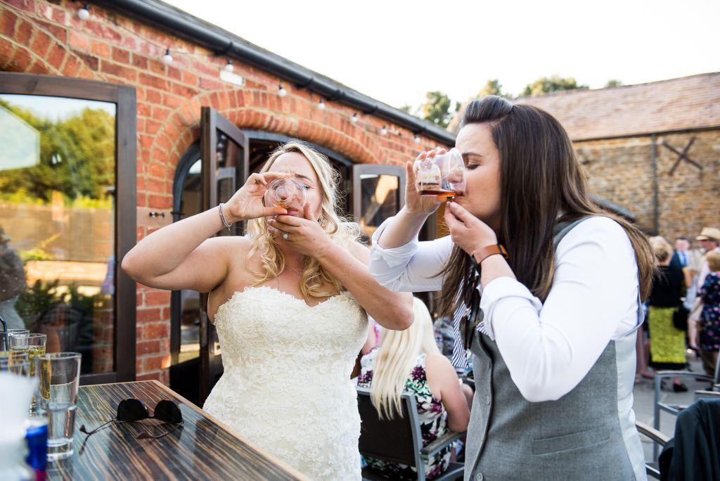 LGBT wedding photography, brides do shots at the bar together
