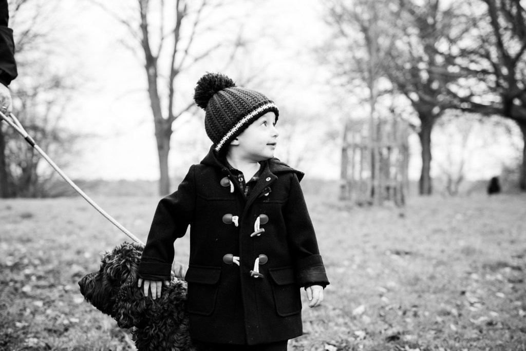 family photography guildford, black and white photograph of little boy stroking a dog