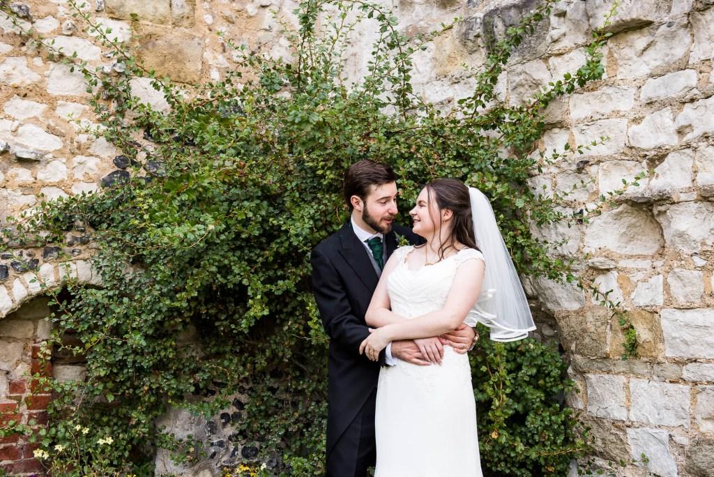 Alternative wedding photography - couple embrace in Guildford castle gardens
