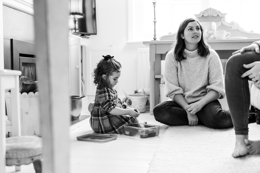 London family photography, black and white image of a little girl and mother sitting on the floor