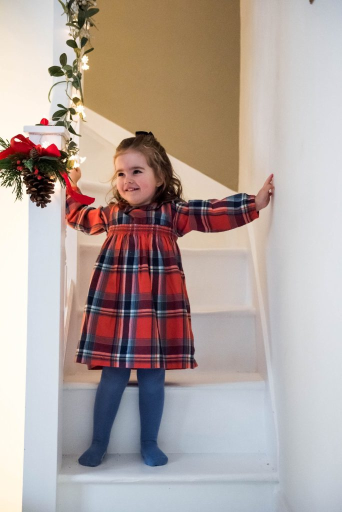 Little girl dressed in a tartan dress on the stairs