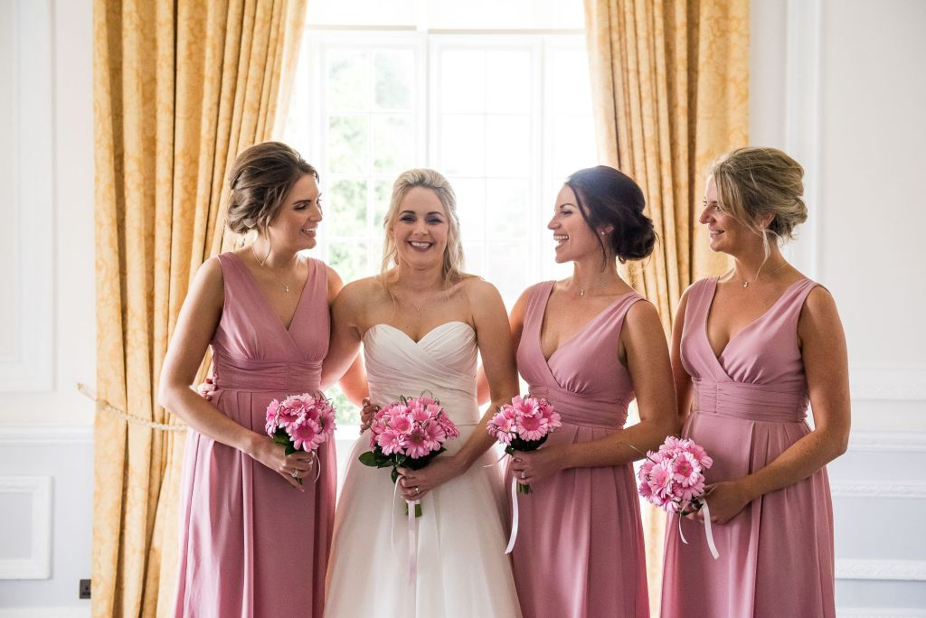 bride with her bridesmaids, dressed in matching soft pink midi dresses