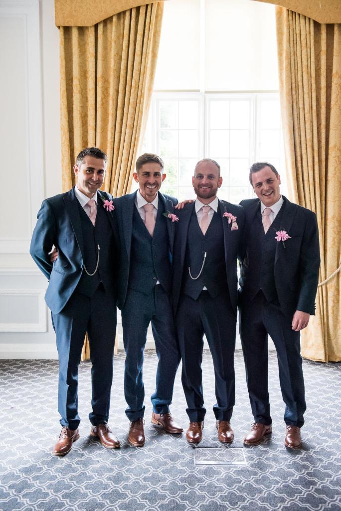 groomsmen in matching three piece suits and pink handkerchiefs