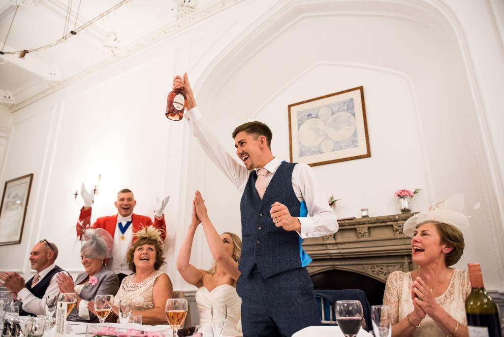 st martha's wedding, groom raises champagne bottle