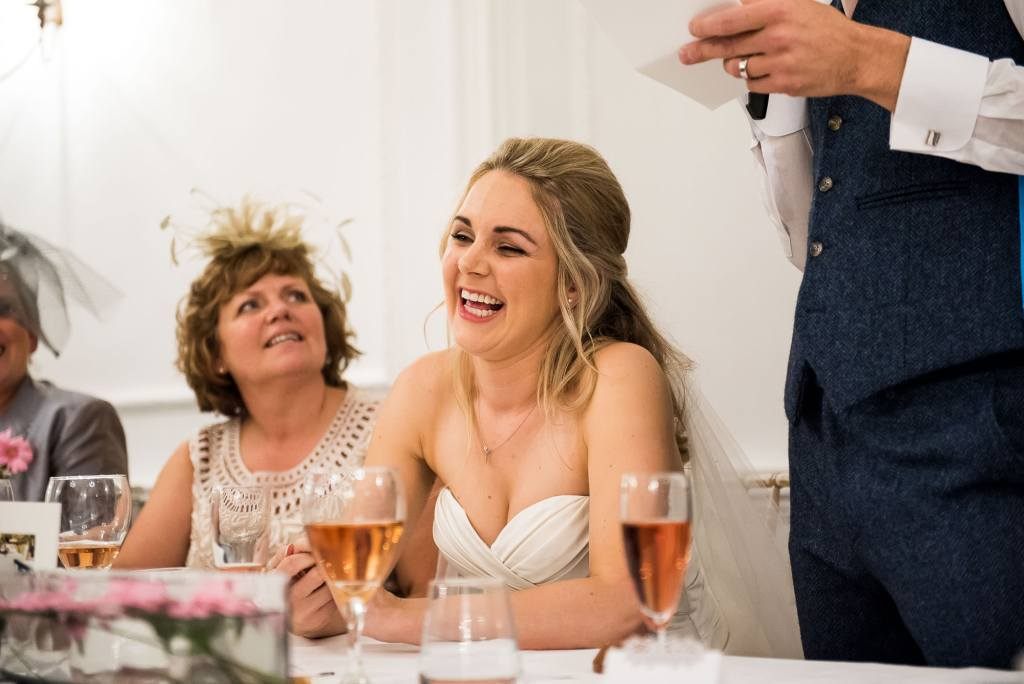 bride laughs sweetly at groom's speech