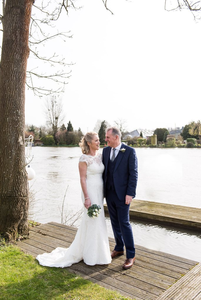 Couple stand beside each other beside the river