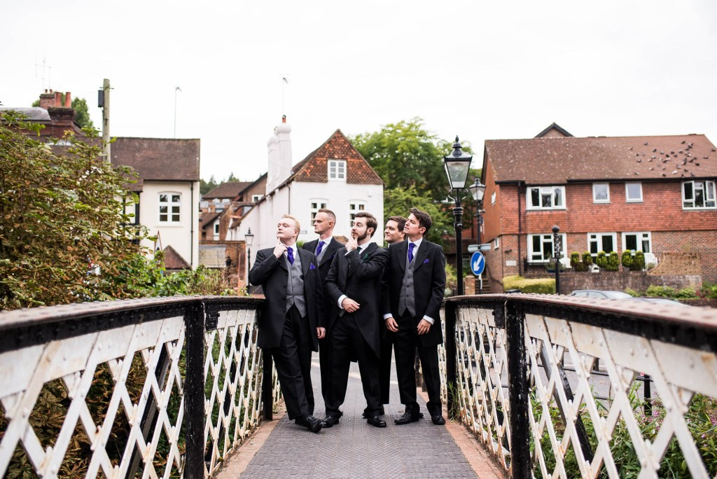 Groomsmen pose for comical group photographs before the wedding ceremony
