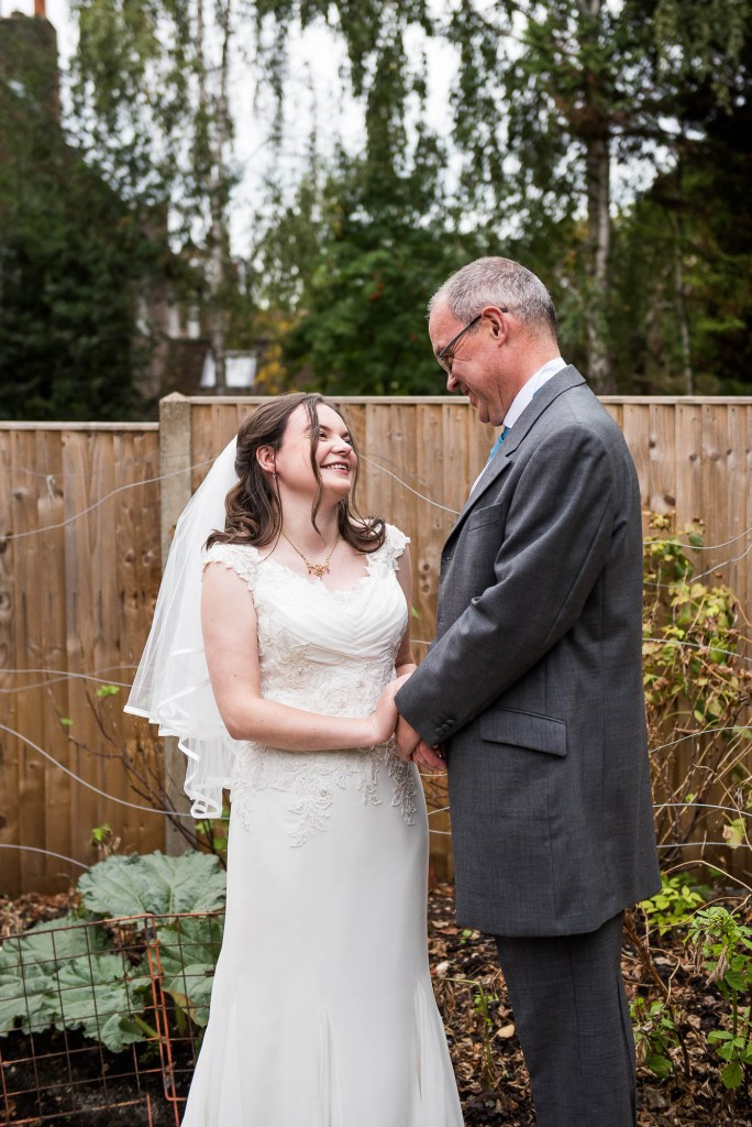Bride and her father smile lovingly at one another