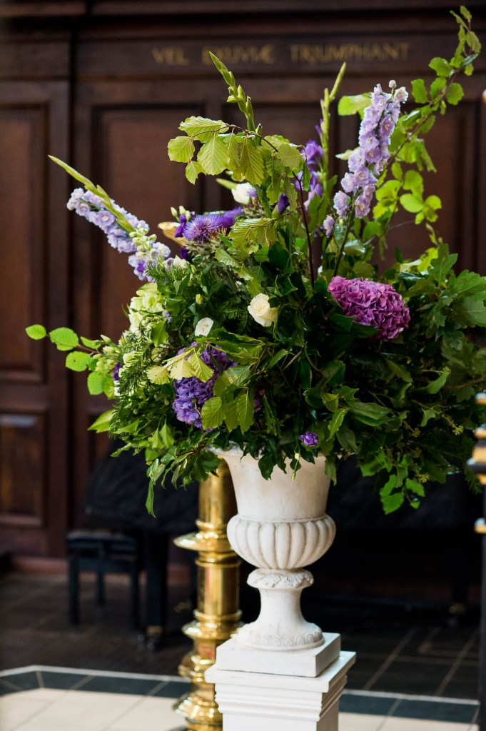 Purple, green and white ceremony flowers in rustic arrangements