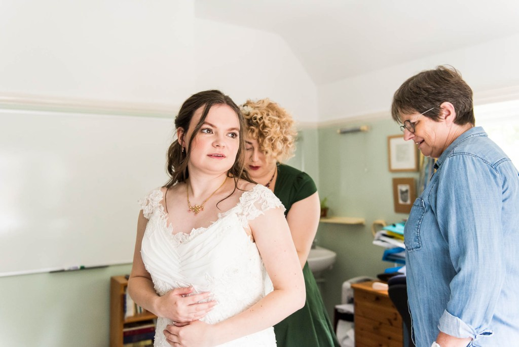 Surrey wedding as relaxed bride puts on her lace wedding dress, Documentary wedding photographer surrey