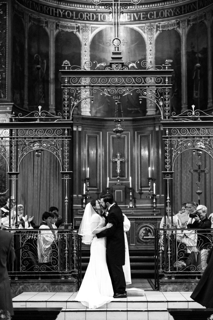 Bride and groom share passionate first kiss during Holy Trinity Church ceremony in Surrey