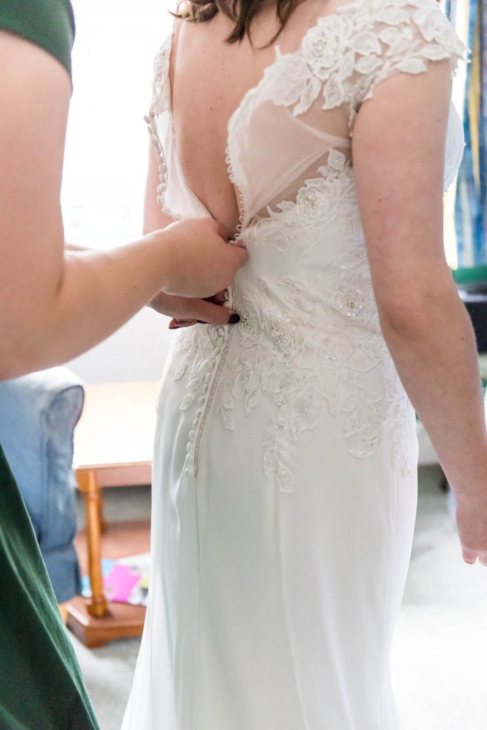 Surrey bride has lace buttons done up