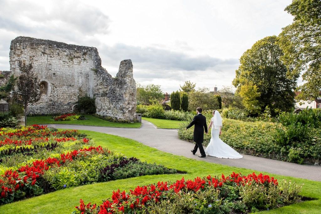 Couple walk through Guildford Castle gardens together in evening golden hour light