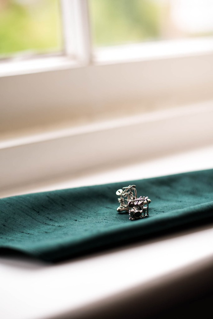 Wedding details - Cufflinks sit on a green wedding pocket square