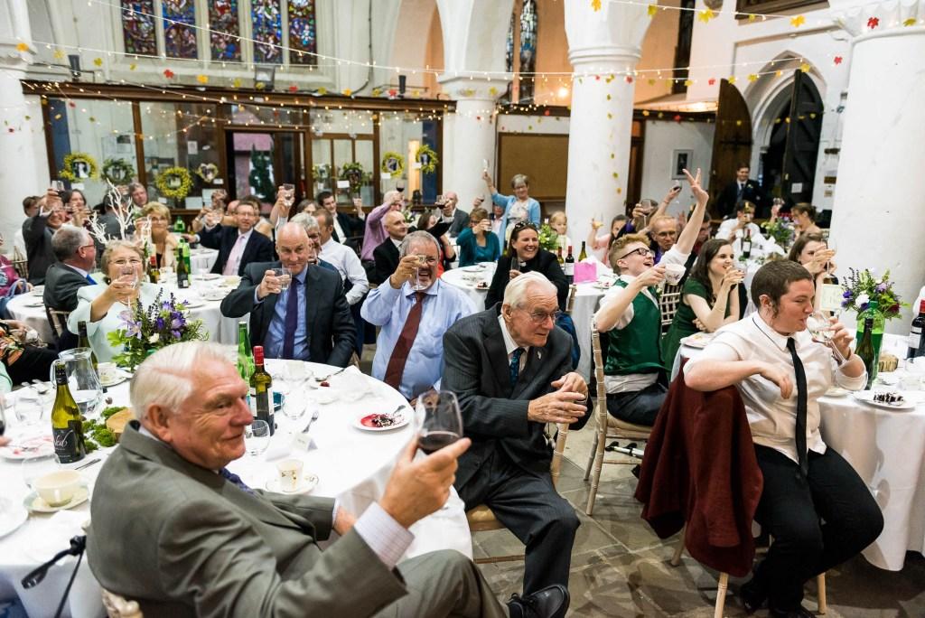 Documentary wedding photographer surrey, Wedding party raise a toast to the happy couple