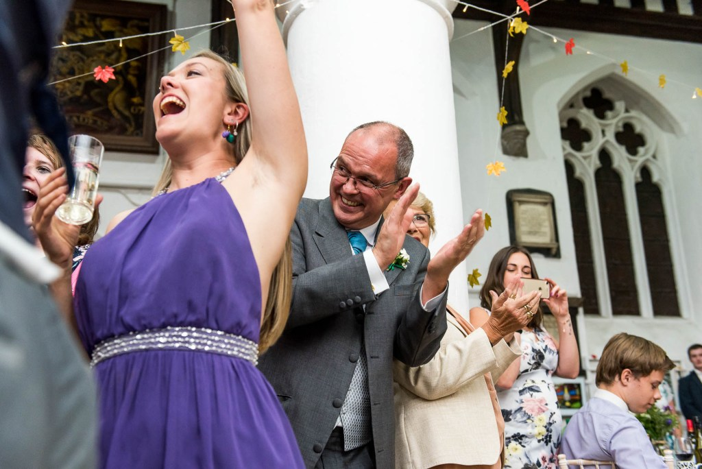 Documentary wedding photographer surrey - Cheering guests smile and clap at first dance