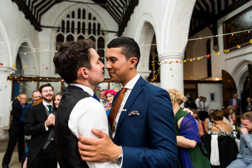Gay couple share loving moment together on the dance floor. Documentary wedding photographer surrey