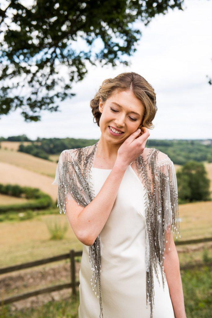 Bride smiles sweetly in silk wedding dress at Botley Hill Barn Farm