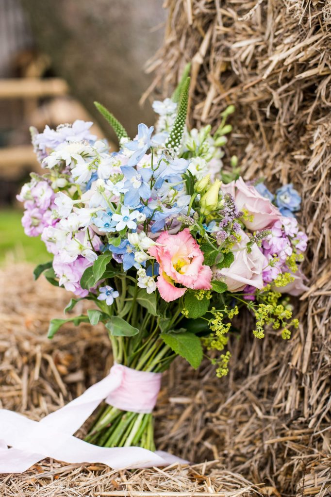 Soft pastel coloured floral arrangement with silk ribbon for Surrey wedding styled shoot