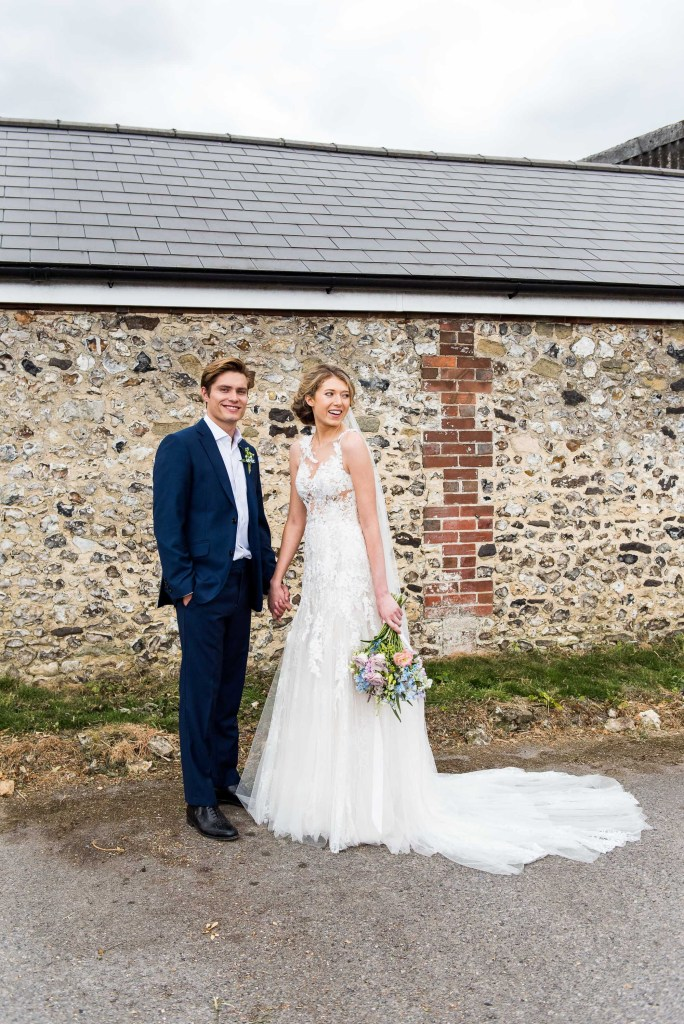 Gorgeous couple stand hand in hand in front of stone barn