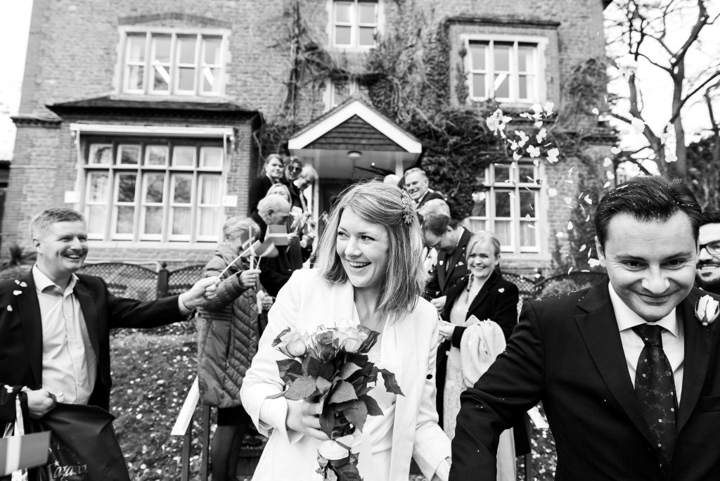 Black and white image of wedding couple exiting the confetti line