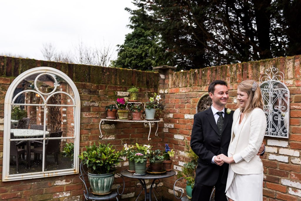 Bride and groom stand candidly in creative pub garden