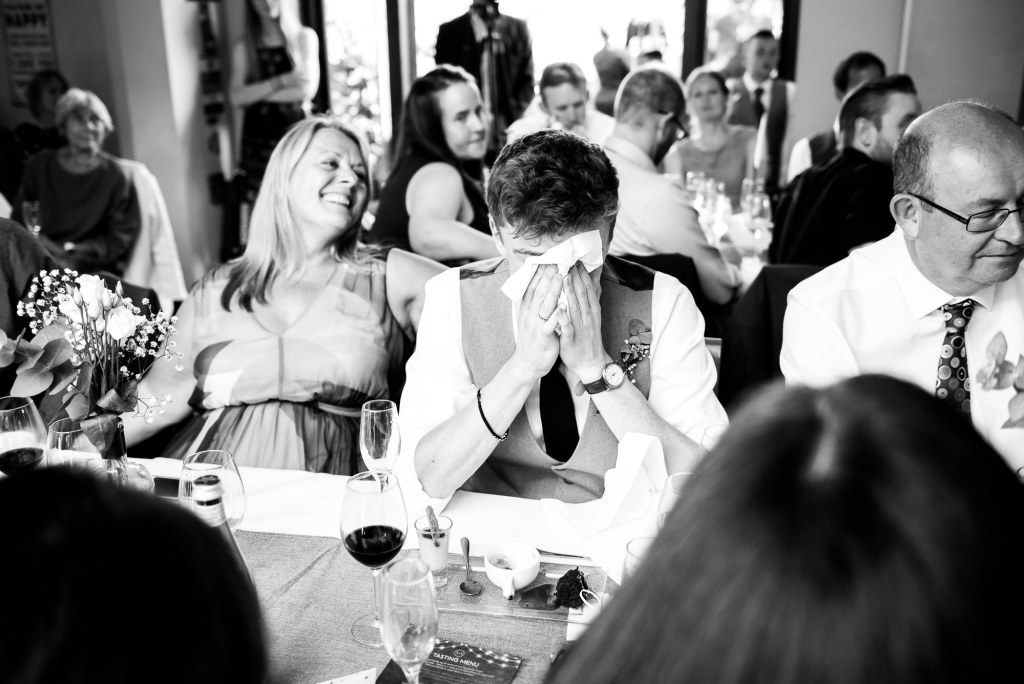 How to choose a wedding photographer // emotional guest hides his face in napkin during wedding speeches