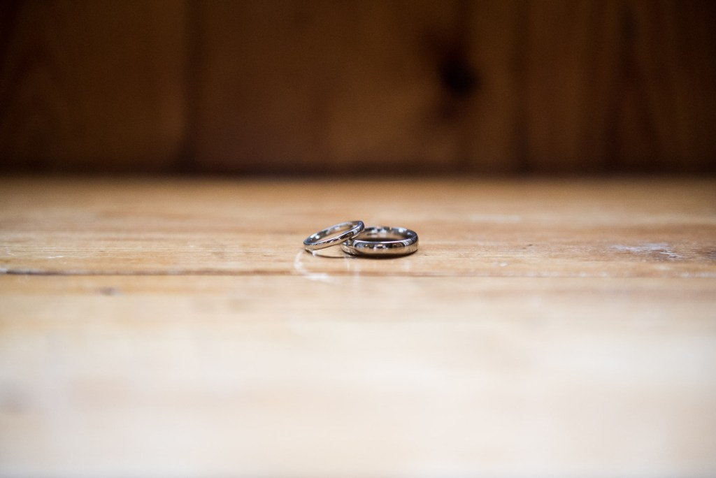 wedding rings placed together on wooden surface, groom preparation photography