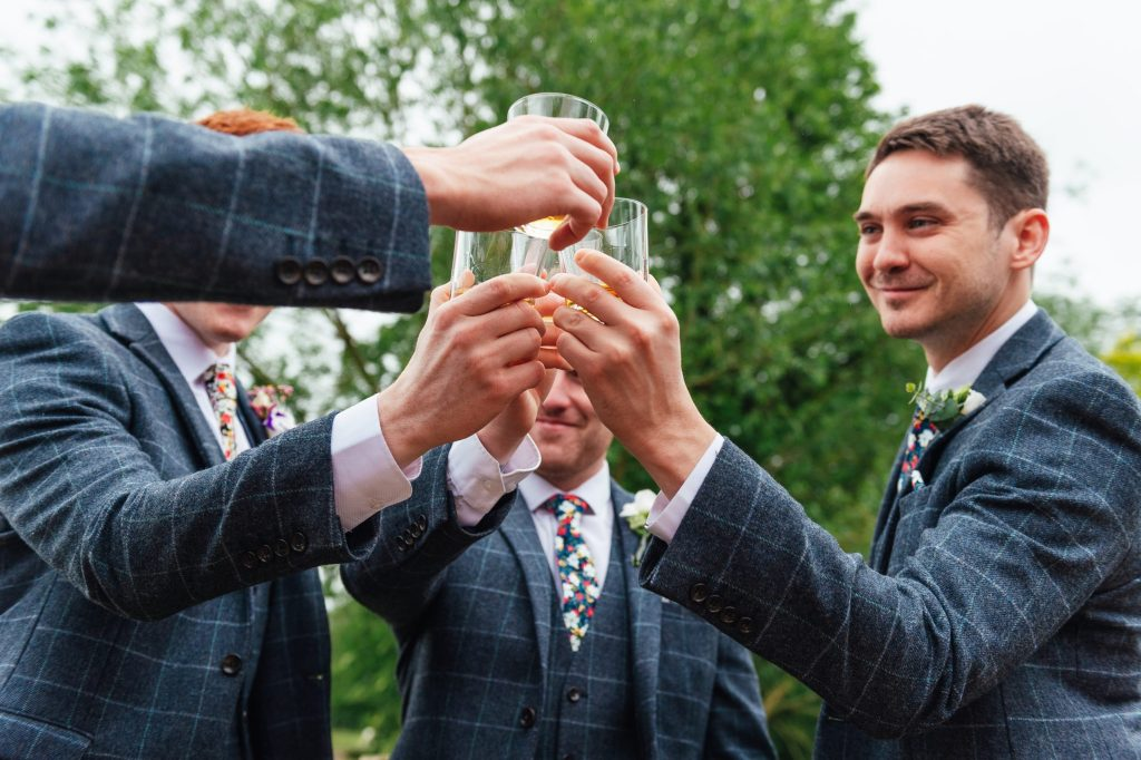 Groomsmen cheers together on a wedding morning