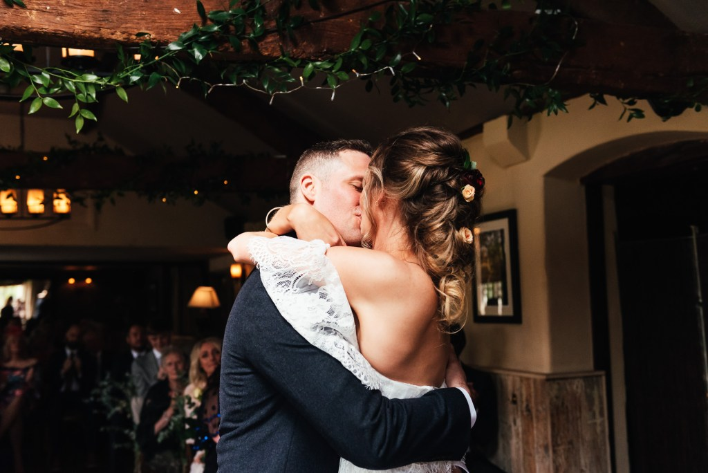Bride and groom share a passionate first kiss at their The Mill at Elstead Wedding