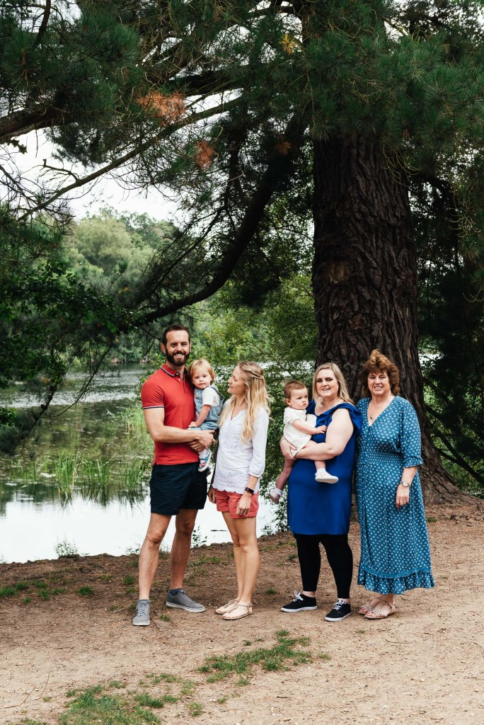 Family stand together in front of Virginia Water Lake