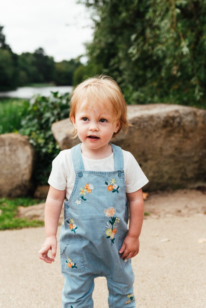 Natural portrait, toddler is wearing cute floral dungarees and a white top
