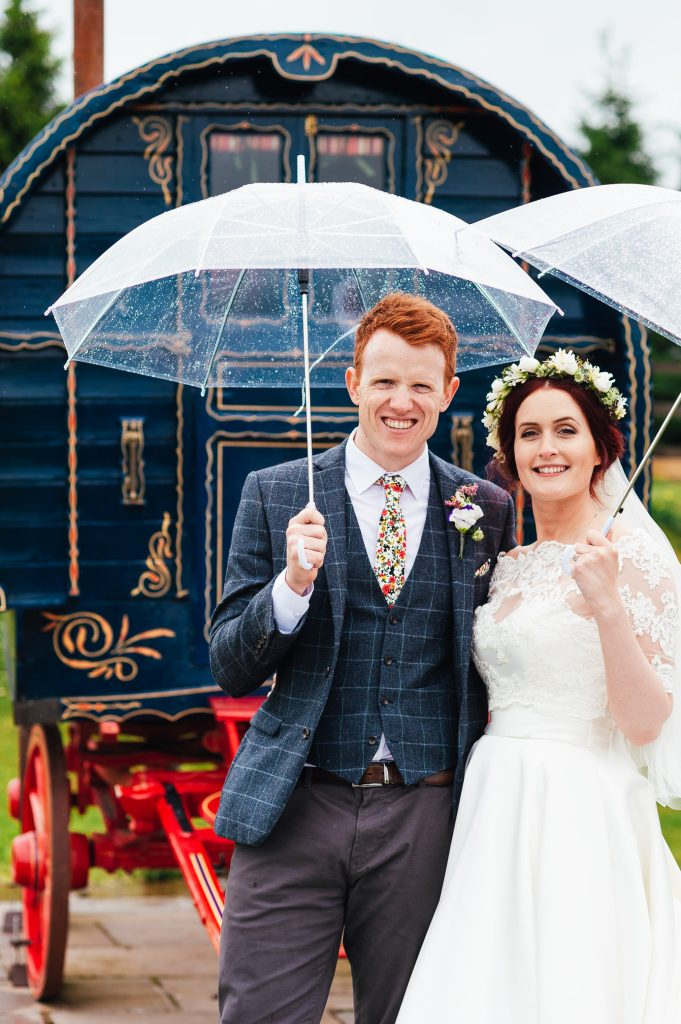 Couple stand with umbrellas outside, rainy yorkshire wedding photography