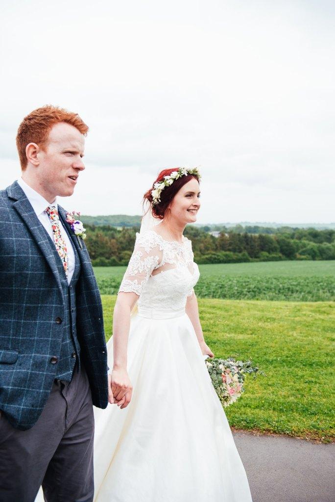 Bride and groom walk hand in had at Deepdale Farm wedding