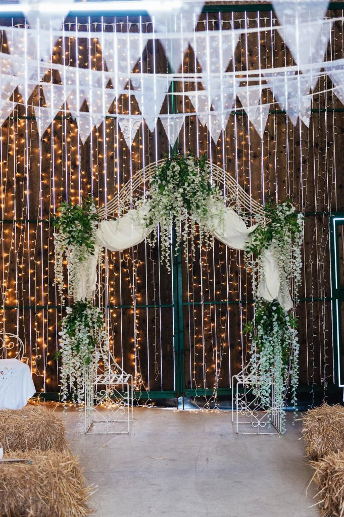 Fairy light backdrop with foliage flower arch