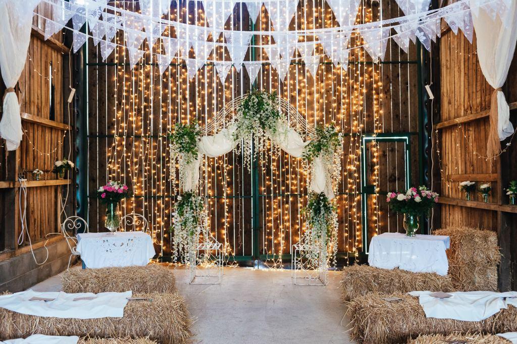 Fairy light backdrop with foliage flower arch, Deepdale Farm Barn wedding