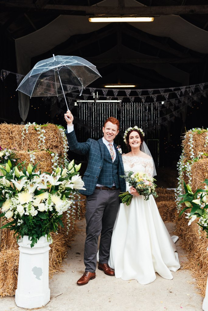 Bride and groom pose with umbrella for their Deepdale Farm wedding