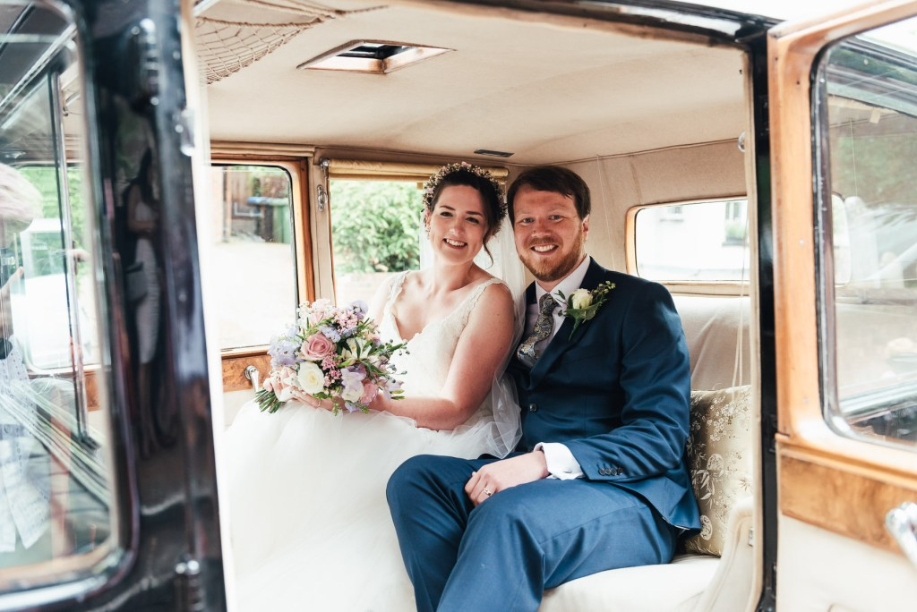 Bride and groom smile inside their vintage wedding car