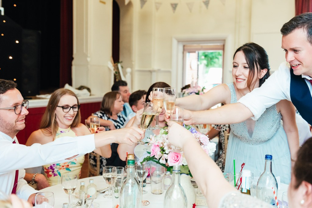 Glasses touch in a cheers during wedding speeches