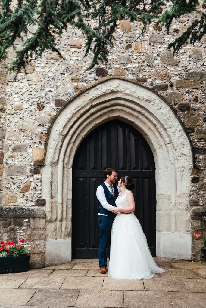 Bride and groom couples portrait with beautiful church door