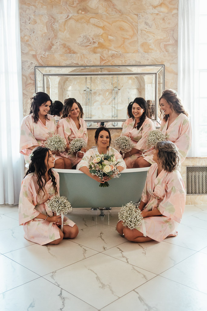 Bride and her bridesmaids pose in the grand bath tub