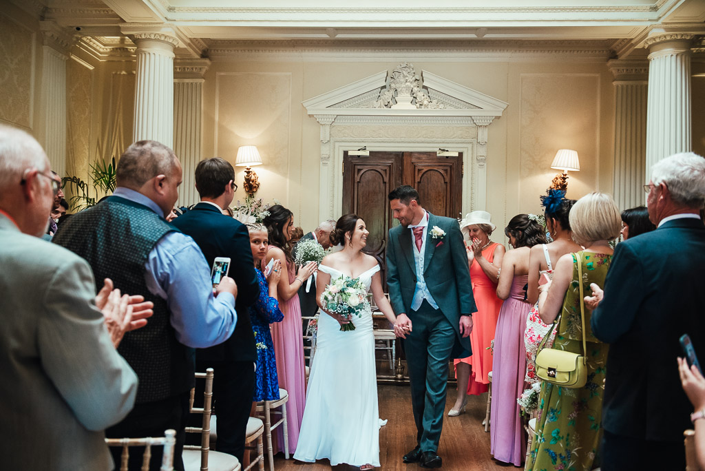 Bride and groom walk down the aisle for the first time as husband and wife