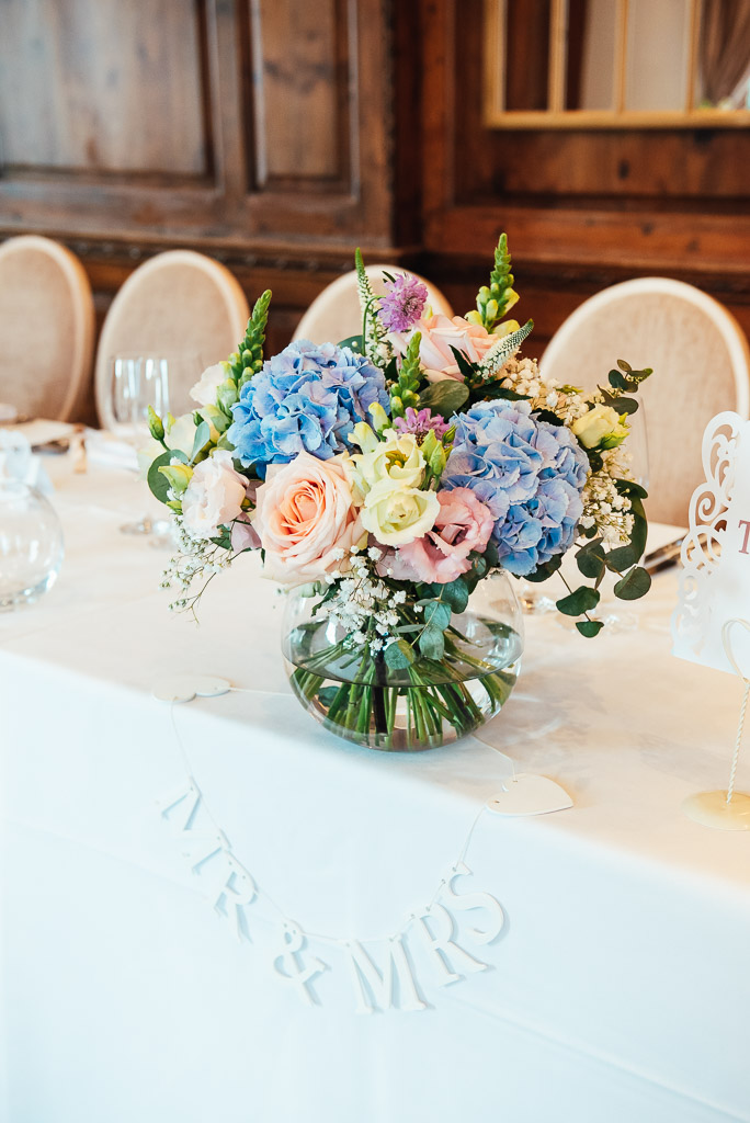 Beautiful table setting flower bouquets with blue hydrangea and pink roses