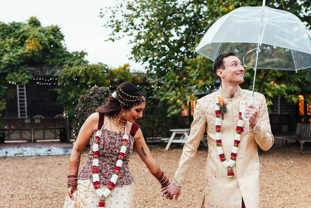 Beautiful Hindu bride and her husband take a walk together at South Farm in the rain