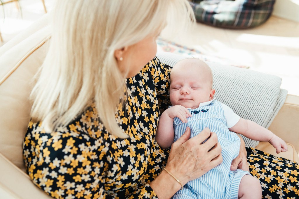 Grandmother holds her grandson in gorgeous airy and bright conservatory