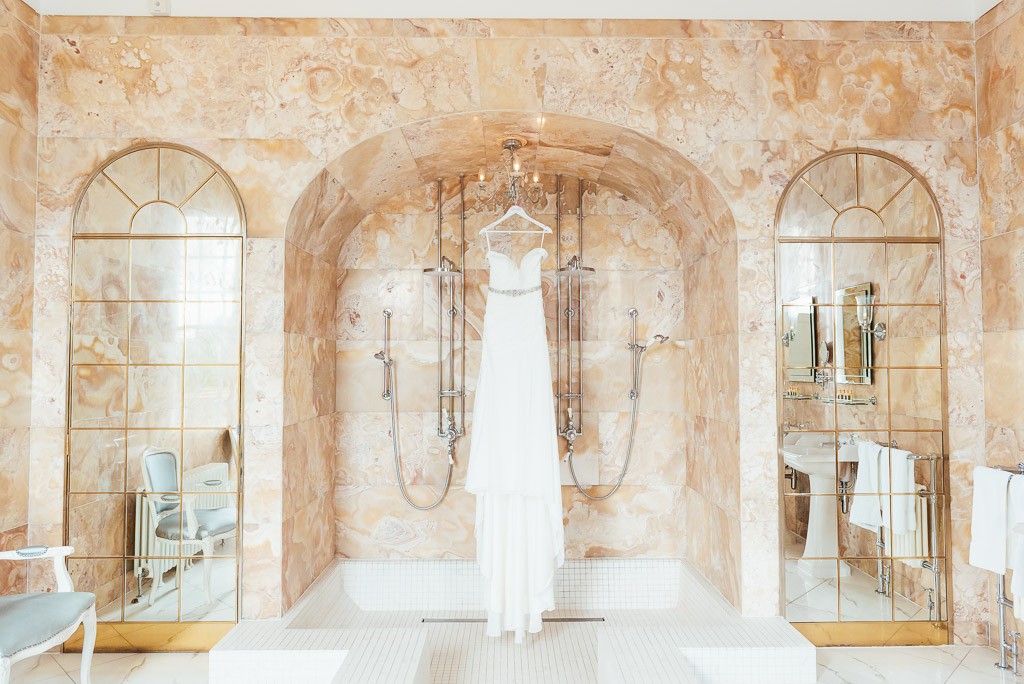 Beautiful wedding dress in glamorous marble bathroom