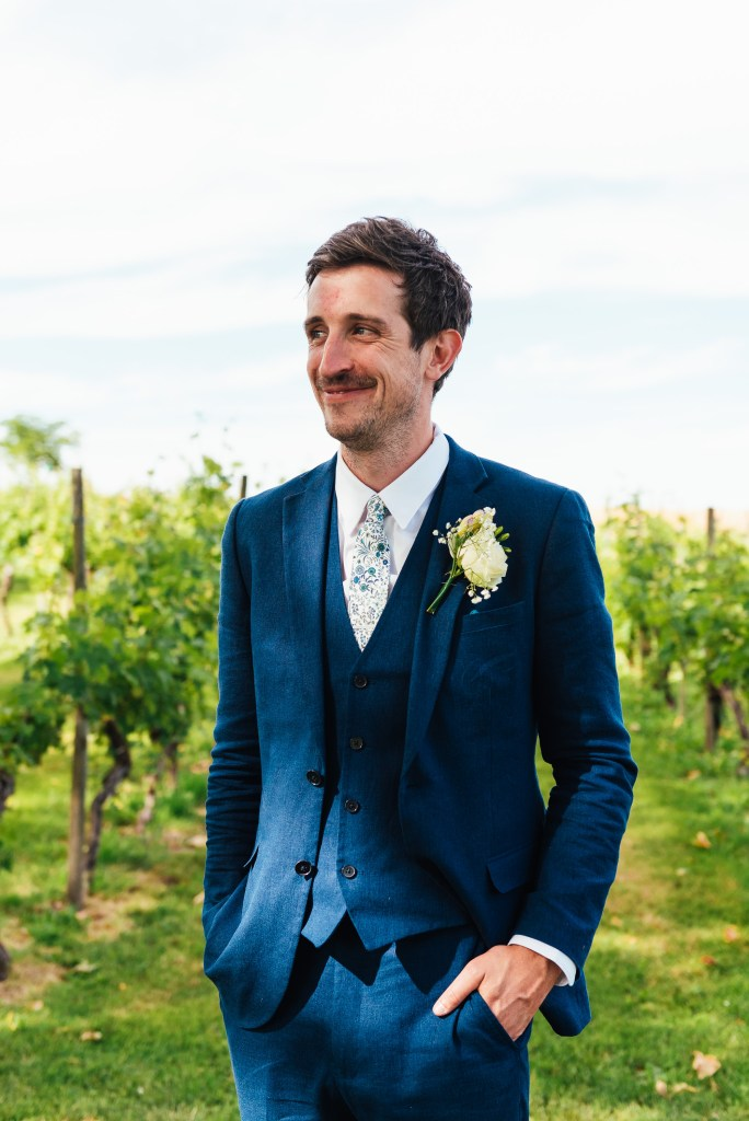 Handsome groom in a tailored navy blue three piece suit with home made button hole