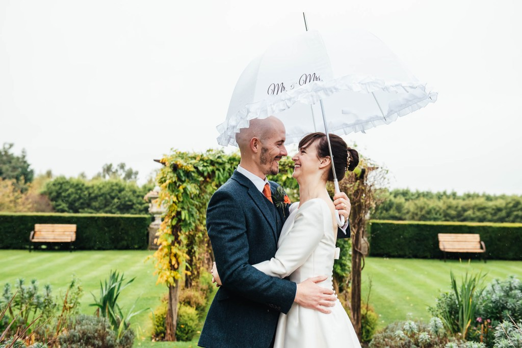 Couple embrace each other in the rain under an umbrella at their Surrey wedding